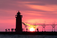 The South Haven lighthouse makes a striking silhouette againt the setting sun and the cotton candy swirl of clouds