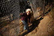Jean Bogiages, a resident of Potrero Hill, goes through a hole in the fence many homeless use to access the hill over Highway 101 where they camp in San Francisco, Calif., Friday, October 16, 2015.
