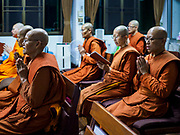 13 JANUARY 2019 - NAKHON PATHOM, THAILAND:  Female monks at Wat Songdhammakalyani participate in a chanting service before going out on their alms rounds. The Sangha Supreme Council, Thailand's governing body of Buddhist monks, bans the ordination of female monks, but hundreds of Thai women have gone abroad, mostly to Sri Lanka and India, to be ordained. There are about 270 women monks in Thailand and about 250,000 male monks. There are 7 monks and 6 novices at Wat Songdhammakalyani in Nakhon Pathom. It was the first temple in Thailand to have female monks. The temple opened 60 years ago and has always been a temple of women monks. Women can be ordained as novices in Thailand, but to be ordained as a full monk would require the participation of 10 female monks and 10 male monks, and male monks in Thailand are barred from participating in women's ordination ceremonies.     PHOTO BY JACK KURTZ