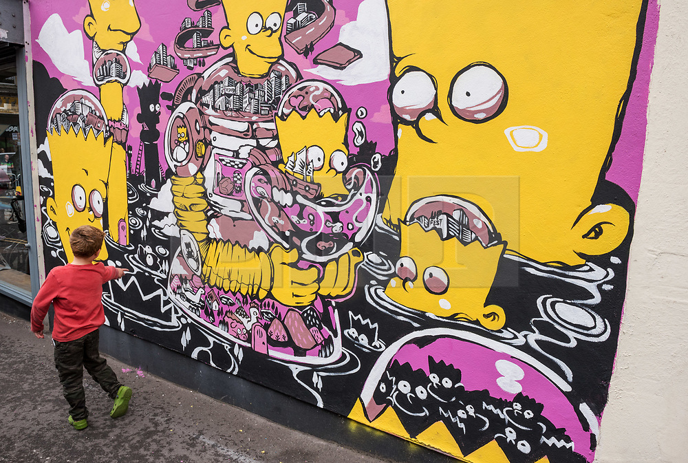 © Licensed to London News Pictures.  28/07/2018; Bristol, UK. Upfest, The Urban Paint Festival, 2018 with themes this year including the Simpsons cartoon series and 100 years of the first women getting the vote. A piece of work by BAO pictured with characters from the Simpsons including Bart Simpson. Upfest which is Europe's largest Street Art and Graffiti Festival takes place in the Bedminster area of Bristol between Saturday the 28th and Monday 30th of July. In celebration of their 10th anniversary, Upfest will feature the animated family, The Simpsons with 2018 festival goers treated to artist interpretations including Homer, Marge, Bart, Lisa, and Maggie. The festival has also teamed up with Bristol Women's Voice to celebrate the centenary of the first votes for women, and together Upfest and Bristol Women's Voice will celebrate the progress made since 1918, with three artists including Nomad Clan chosen to portray the suffrage movement and the rights of women. Upfest will have 400 artists from 70 countries in attendance, including this year's lead artists Insane51, L7m, London Police, Nomad Clan, Odeith, and Paris. This year, three Upfest artists have been selected by The Simpsons creator Matt Groening to bring The Simpsons to life in their own unique styles: Bao, born and based in Hong Kong, is known for her freestyle work with vibrant murals and illustrations; Soker, a wildstyle writer, is one of Bristol's finest talents and has been putting his mark on the city since the late 80's; Nomad Clan, the collective of Cbloxx and AYLO, one of the most sought-after duos in the international global street art scene. Upfest will be raising money for The National Association for Children of Alcoholics (NACOA) which offers aid and assistance for children growing up in families affected by alcoholism. Photo credit: Simon Chapman/LNP
