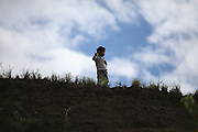 A boy plays with a straw cross near San Jose village. Toledo Cacao Growers' Association (TCGA), San Jose, Toledo, Belize. January 25, 2013.