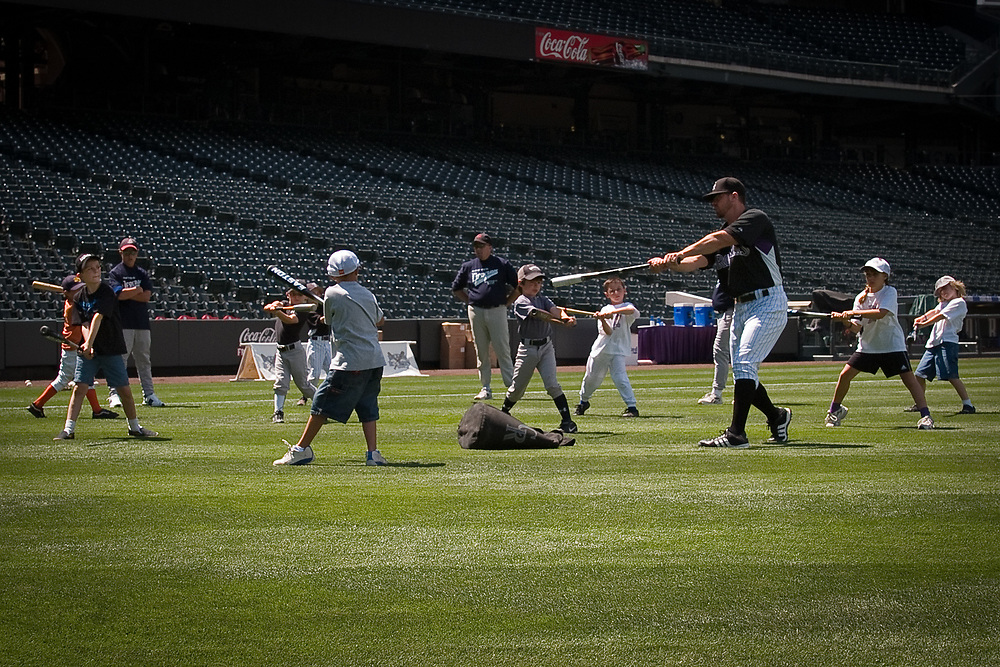 MIKE BARD, Colorado Rockies Assistant Hitting Coach, leads a group of eight and nine year-olds in practice swings.