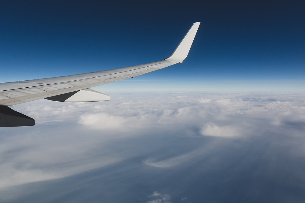 The wing tips of a jetliner cruising over the Atlantic Ocean off the coast of the eastern United States.