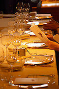 A table set with plates wine glasses and cutlery. A guest holding up and reading the menu in anticipation of the meal. In the restaurant Michel Chabran i Pont de l'Isere. Pont de l'Isere Isère, Drome Drôme France, Europe