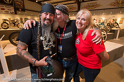 Jack Schitt with Cheryl and Mailman Kevin O'Brien on the Industry party night for Michael Lichter's tattoo themed Skin & Bones Motorcycles as Art exhibition at the Buffalo Chip during the annual Sturgis Black Hills Motorcycle Rally.  SD, USA.  August 7, 2016.  Photography ©2016 Michael Lichter.