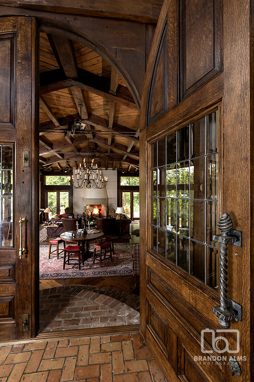 Large doors that peek into a large fireplace room. Photo by Brandon Alms Photography