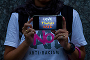 """A Japanese activist holds a smart phone with the message """"Love Trumps Hate"""" as she joins other  American and Japanese  people at the  """"Enough is Enough"""" rally in Toranomon, Tokyo Japan, Tuesday August 15th 2017. Around 20 people gathered to take part in a global day of action demanding fairer policies in the United States that do not favour only the rich and do not remove human rights from ordinary people. A silent vigil was held for 30 minutes at 6pm so that the voices that could be heard after spoke louder. This is the closest it is possible to protest to the US embassy in Tokyo."""