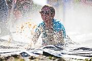 A girl slides down a Slip 'n Slide at the 2012 Bolder Boulder 10K road race in Boulder, Colorado.