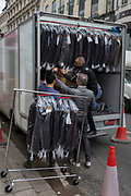 A team of workmen unload menswear and suits hanging on rails and in boxes, from a small van on Conduit Street, on 8th March 2018, in London, England.