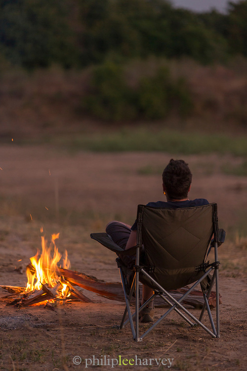 Tourist sitting by campfire at night, South Luangwa National Park Nsefu Sector, Zambia
