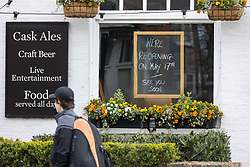 © Licensed to London News Pictures. 11/04/2021. London, UK. Members of the public walk past a pub in Wimbledon Village, South West London displaying a sign that it won't be opening until Monday 17th May as pubs and shops across England get ready for the lifting of Covid-19 restrictions tomorrow. Prime Minister Boris Johnson announced last week that non-essential shop, restaurants with outside seating , hairdressers and gyms can reopen tomorrow, Monday 12 April 2021 after 4 months of Covid-19 lockdowns. Photo credit: Alex Lentati/LNP