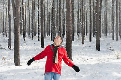 man enjoying snow falling in the woods