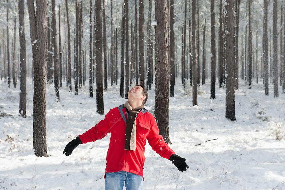 man enjoying snow falling in the woods