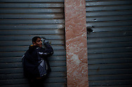 A boy looks at bullet holes from mercenary forces in Banghazi on Feb. 25, 2011.