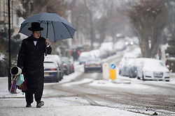 © Licensed to London News Pictures. 01/03/2018. London, UK. An Orthodox Jewish man carrying an umbrella through snow covered street in Stamford Hill in north London before the local jewish community celebrate the festival of Purim. . Purim celebrates the miraculous salvation of the Jews from a genocidal plot in ancient Persia, an event documented in the Book of Esther. Traditionally the jewish community wear fancy dress and exchange reciprocal gifts of food and drink. Photo credit: Ben Cawthra/LNP