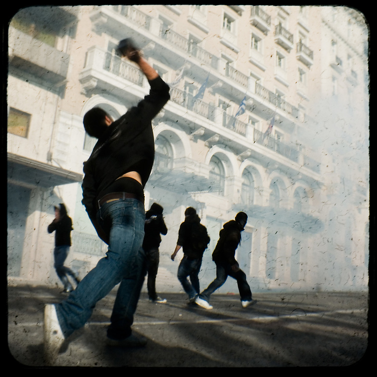 Rioting in front of King George hotel in Syntagma Athens. <br /> <br /> Following the murder of a 15 year old boy, Alexandros Grigoropoulos, by a policeman on 6 December 2008 widespread riots, protests and unrest followed lasting for several weeks and spreading beyond the capital and even overseas<br /> <br /> When I walked in the streets of my town the day after the riots I instantly forgot the image I had about Athens, that of a bustling, peaceful, energetic metropolis and in my mind came the old photographs from WWII, the civil war and the students uprising against the dictatorship. <br /> <br /> Thus I decided not to turn my digital camera straight to the destroyed buildings but to photograph through an old camera that worked as a filter, a barrier between me and the city.