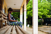 Aya Solange Siallo, 24, sits on a bench while waiting for the results of the HIV test at the NDA health center in Dimbokro, Cote d'Ivoire on Friday June 19, 2009. Aya, who's pregnant of a second child, tested positive.