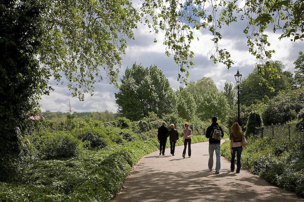 5 people walking along path in Hyde park, london in the sunshine