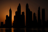 UNITED ARAB EMIRATES, DUBAI - CIRCA JANUARY 2017: Silhouette of the Dubai Marina cityscape and skyscrapers as seen from Palm Jumeirah at sunrise.