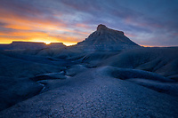 Sunset over Factory Butte and the eroded badlands of the San Rafael Swell in sourthern Utah, USA
