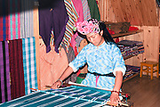 China Yunnan province Lijiang A young lady in traditional Naxi dress hand weaving scarves in the ancient city