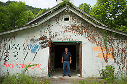 """Just down the road from Lindytown, West Virginia, Leo Cook stands in the doorway of the now-vandalized building that once served as the meeting hall for members of Local 8377 of the United Mine Workers of America. Back when the building was in use, Cook sometimes polished its wooden floors. Mountaintop-removal mines are now abundant in the area. Mountaintop Removal is a method of surface mining that literally removes the tops of mountains to get to the coal seams beneath. It is the most profitable mining technique available because it is performed quickly, cheaply and comes with hefty economic benefits for the mining companies, most of which are located out of state. Many argue that they have brought wage-paying jobs and modern amenities to Appalachia, but others say they have only demolished an estimated 1.4 million acres of forested hills, buried an estimated 2,000 miles of streams, poisoned drinking water, and wiped whole towns from the map. The mountaintop-removal mine near Blair caused the population to fall from 700 in the 1990s to fewer than 50 today, according to the Blair Mountain Heritage Alliance. """"I saw Lindytown disappear,"""" Leo Cook said. """"Three people up there that died, and I believe in my soul -- I'll go to my grave believin' this?that aggravation's what caused it."""" © Ami Vitale"""