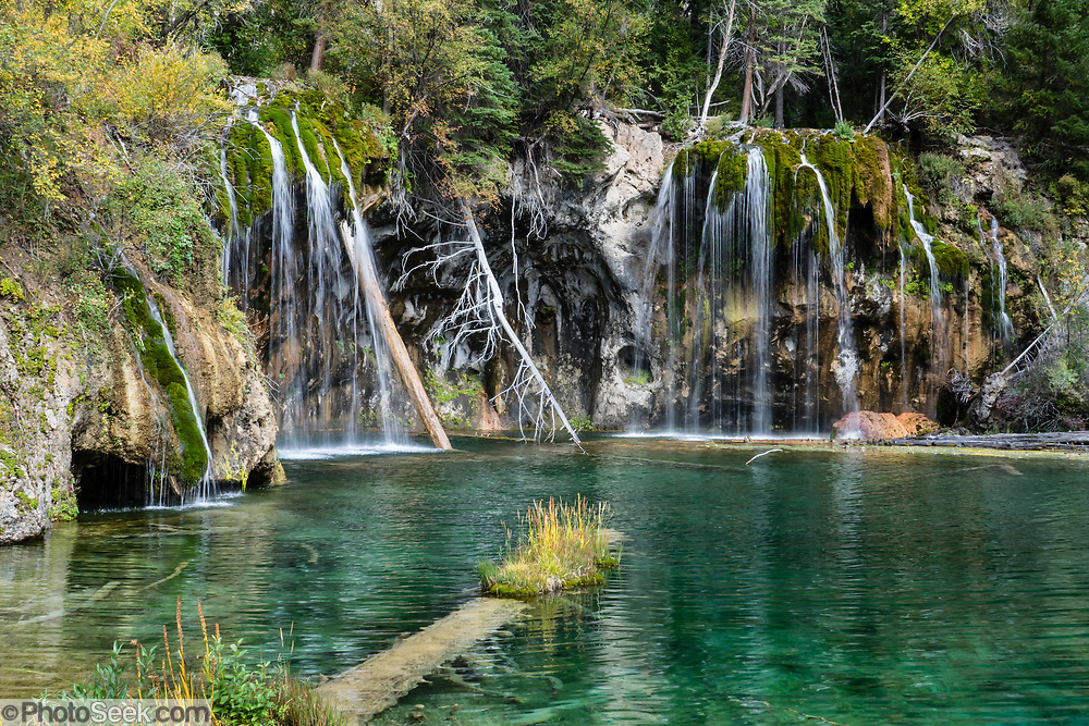 Hanging Lake, along East Fork Dead Horse Creek in Glenwood Canyon, White River National Forest, Colorado, USA. From the trailhead 7 miles east of Glenwood Springs along Interstate 70, follow the Glenwood Canyon Bike and Pedestrian Path east then ascend Dead Horse Creek (a tributary of the Colorado River), for 4 miles round trip gaining 1200 feet, including the nice side trip to Spouting Rock falls. Dissolved carbonate minerals color its water turquoise. The fragile shoreline is travertine, created when dissolved limestone from the Mississippian Period Leadville Formation is deposited in layers on rocks and logs. The shallow bed of Hanging Lake formed on a fault line where the valley floor above sheared and dropped.