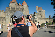 tourist making film of castle tourist attraction Carcassonne La Cite