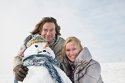Portrait of couple with snowman, smiling, Bavaria, Germany