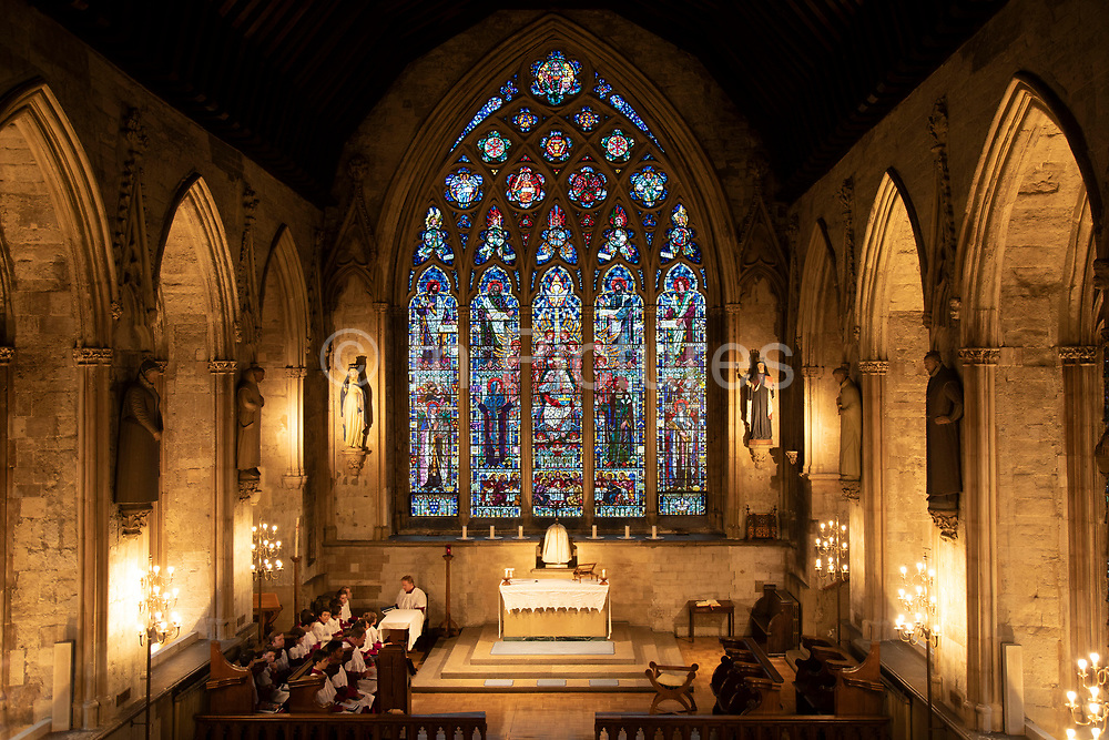 Choir practice beside the stained glass window in the main chapel at St Etheldreda's Church in London, England, United Kingdom. St Etheldreda's Church was the town chapel of the Bishops of Ely from about 1250 to 1570. It is the oldest Catholic church in England and one of only two remaining buildings in London from the reign of Edward I. It was once one of the most influential places in London with a palace of vast grounds. It was like an independent state, the Bishop of Ely's place in London or Ely Place as it is now called, and its chapel took its name from one of England's most popular saints of the day, Etheldreda.