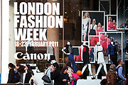 Shoppers pass a sign for London Fashion Week  outside on the busy Regent Street.