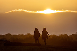 © Licensed to London News Pictures. 17/12/2020. London, UK. Walkers and families enjoy the magnificent sunrise in Richmond Park, South West London this morning on the second day of Tier 3 for parts of the South East of England as the government agonise over further restrictions for the Christmas period. Today, Health Secretary Matt Hancock will announce the latest updates on the government's tiering system as health officials put the pressure on the government not to reduce tier levels before Christmas. London was put into Tier 3 Very High Alert yesterday (Wednesday) after a new Covid-19 variant was discovered. Photo credit: Alex Lentati/LNP