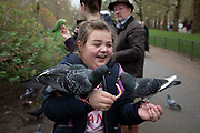 Young tourists feeding the birds in St Jamess Park laughing in pleasure and joy as she has several pigeons land on her in London, United Kingdom.