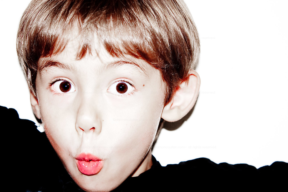 A young boy to the left edge of the frame pulls a funny face.