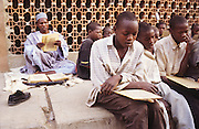 Islamic school on the pavement for boys and youths in Kano..The implementation of Islamic Sharia Law across the twelve northern states of Nigeria, centres upon Kano, the largest Muslim Husa city, under the feudal, political and economic rule of the Emir of Kano. Islamic Sharia Law is enforced by official state apparatus including military and police, Islamic schools and education, plus various volunteer Militia groups supported financially and politically by the Emir and other business and political bodies. Fanatical Islamic Sharia religious traditions  are enforced by the Hispah Sharia police. Deliquancy is controlled by the Vigilantes volunteer Militia. Activities such as Animist Pagan Voodoo ceremonies, playing music, drinking and gambling, normally outlawed under Sharia law exist as many parts of the rural and urban areas are controlled by local Mafia, ghetto gangs and rural hunters. The fight for control is never ending between the Emir, government forces, the Mafia and independent militias and gangs. This is fueled by rising petrol costs, and that 70% of the population live below the poverty line. Kano, Kano State, Northern Nigeria, Africa