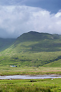 Small white solitary crofters cottage nestling below mountain range by loch on Isle of Mull in the Inner Hebrides and Western Isles of Scotland