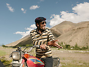 Young Wakhi discuss on his motorcyle, outside a wedding.