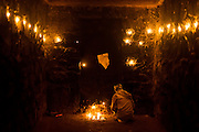 """3rd December 2015, New Delhi, India.  A man at squats at a candlelit shrine dedicated to Djinn worship in the ruins of Feroz Shah Kotla in New Delhi, India on the 3rd December 2015<br /> <br /> PHOTOGRAPH BY AND COPYRIGHT OF SIMON DE TREY-WHITE a photographer in delhi<br /> + 91 98103 99809. Email: simon@simondetreywhite.com<br /> <br /> People have been coming to Firoz Shah Kotla to pray to and leave written notes and offerings for Djinns in the hopes of getting wishes granted since the late 1970's. Jinn, jann or djinn are supernatural creatures in Islamic mythology as well as pre-Islamic Arabian mythology. They are mentioned frequently in the Quran  and other Islamic texts and inhabit an unseen world called Djinnestan. In Islamic theology jinn are said to be creatures with free will, made from smokeless fire by Allah as humans were made of clay, among other things. According to the Quran, jinn have free will, and Iblīs abused this freedom in front of Allah by refusing to bow to Adam when Allah ordered angels and jinn to do so. For disobeying Allah, Iblīs was expelled from Paradise and called """"Shayṭān"""" (Satan).They are usually invisible to humans, but humans do appear clearly to jinn, as they can possess them. Like humans, jinn will also be judged on the Day of Judgment and will be sent to Paradise or Hell according to their deeds. Feroz Shah Tughlaq (r. 1351–88), the Sultan of Delhi, established the fortified city of Ferozabad in 1354, as the new capital of the Delhi Sultanate, and included in it the site of the present Feroz Shah Kotla. Kotla literally means fortress or citadel."""
