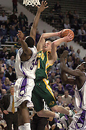 North Dakota State guard Mike Nelson (C) drives to the basket against pressure from Kansas State's Akeem Wright (L) in the first half, during K-State's 82-56 win over North Dakota State at Bramlage Coliseum in Manhattan, Kansas, January 2, 2006.
