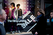 Passers by The Sting sale shop window. London.