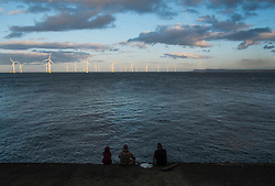 © Licensed to London News Pictures. <br /> 08/03/2015. <br /> <br /> South Gare, Redcar, United Kingdom<br /> <br /> Three friends sit on a sea wall looking out towards the offshore wind farm at South Gare near Redcar as the sun sets behind them.<br /> <br /> Photo credit : Ian Forsyth/LNP