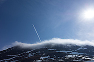 Snow covers the mountains on the road to  Geiraingerfjord in Norway on May 18, 2013.  A jet flies above the fog hovering over a mountain.  (© 2013 Cindi Christie)