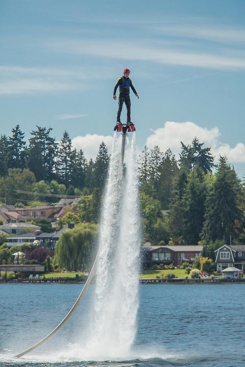 United States, Washington, Kirkland (near Seattle), Man fly boarding on jets of water in Lake Washington