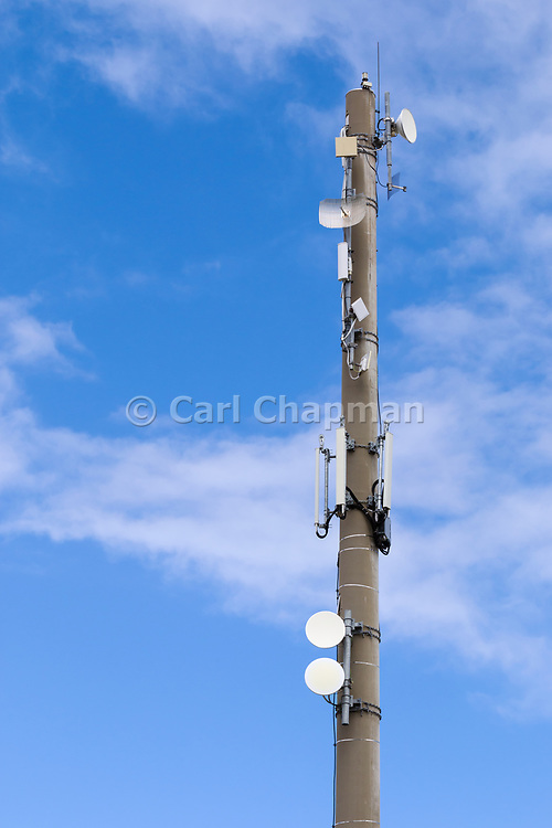 Microwave dish antennas on radio communications  monopole tower for the cellular telephone system. <br /> <br /> Editions:- Open Edition Print / Stock Image