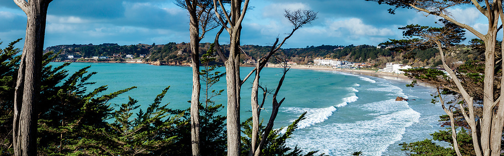 View through the trees of St Brelade's Bay, towards the hotels and restaurants and the surfers in the sea.