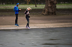 © Licensed to London News Pictures. 10/01/2021. London, UK. A woman tests the thickness of the ice with her foot while running around Regents Park boating lake in central London which has frozen frozen over, as the capital wakes to sub zero temperatures. Photo credit: Ben Cawthra/LNP