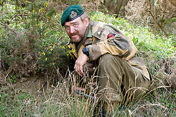 Reenactor from Northern World War Two Association, portraying a Royal Navy Commando, spots for a sniper during an ambush while taking part in a private 24hr excerise.<br /> Sutton Grange, near Ripon Yorkshire 15  May 2010 .Images © Paul David Drabble.