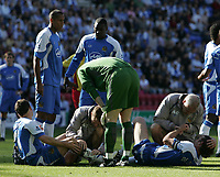 Photo: Andi Thompson.<br />Wigan Athletic v Watford. The Barclays Premiership. 23/09/2006.<br />Wigan's Arjan De Zeeuw (R) and Leighton Baines (L) go down injured.