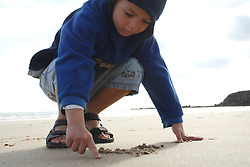 Boy playing on Tynemouth Longsands writing his name; NE England