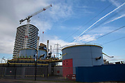 A large crane hovers over the Tidal Basin Pumping Station at Royal Victoria Dock designed by Architect Richard Rogers and built in 1987 on Tidal Basin Road, London, England, United Kingdom.  The pumping station is colourful and intriguing, but completely functional and pumps rainwater off into the River Thames.
